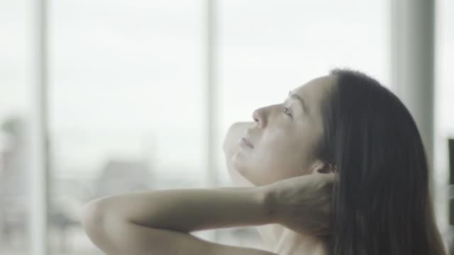 woman leaning head back and running hands through hair - kopf nach hinten stock-videos und b-roll-filmmaterial