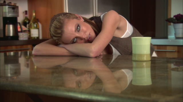 MS Woman leaning on dining table, mug and reflection on table / Jacksonville, Florida, USA