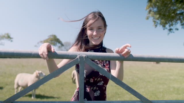 Woman leaning on fence, smiling, looking into camera