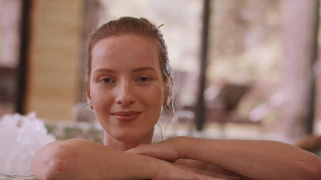 vidéos et rushes de femme s'appuyant sur le bord du jacuzzi - établissement de cure