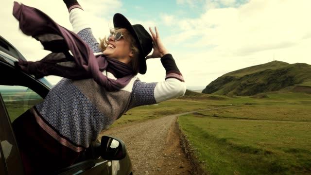 女性が車の窓から傾いています。 - 頭にかぶるもの点の映像素材/bロール