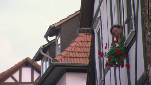 MS LA Woman leaning out window of traditional half-timbered house / Kassel, Germany