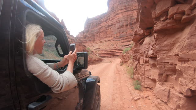 woman leans out of window while driving along red sand road - moab utah stock videos & royalty-free footage