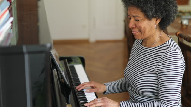 woman learning playing piano at home during covid-19 pandemic - artist stock videos & royalty-free footage