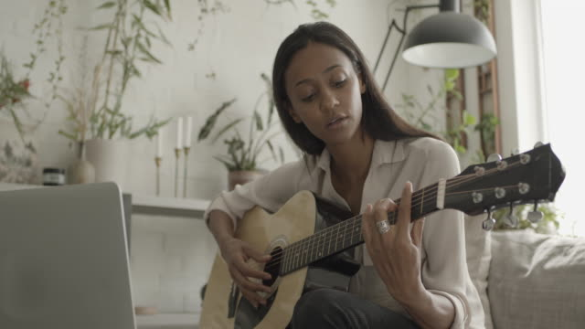 woman learning to play guitar at home - アコースティックギター点の映像素材/bロール