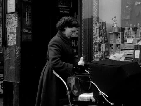 vídeos de stock e filmes b-roll de a woman leaves a chemist shop and walks away pushing a pram - 1955