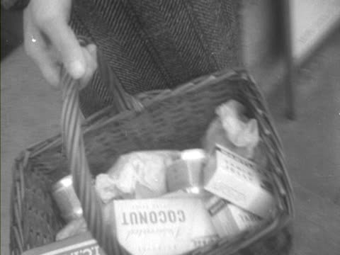 a woman leaves a shop with a basket of shopping - shopping basket stock videos and b-roll footage