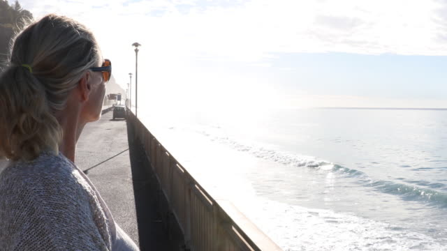 woman leaves car, look out across sea surf - see other clips from this shoot 56 stock videos & royalty-free footage