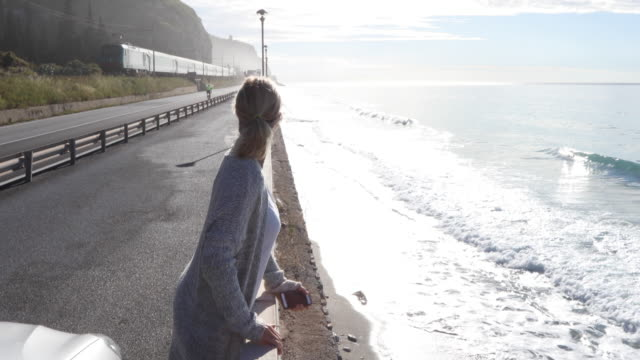 Woman leaves car, look out across sea surf