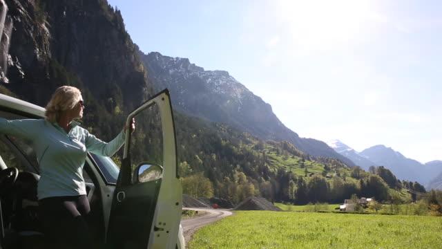 vídeos de stock e filmes b-roll de woman leaves car, look up to distant mountains, waterfall - desembarcar