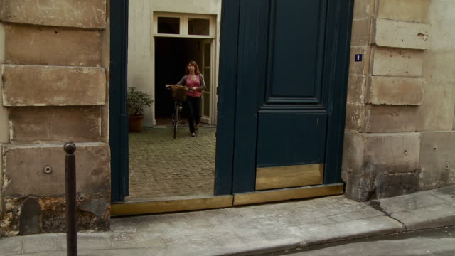 WS PAN Woman leaving apartment and cycling away, Rue des Guillemites, Paris, France