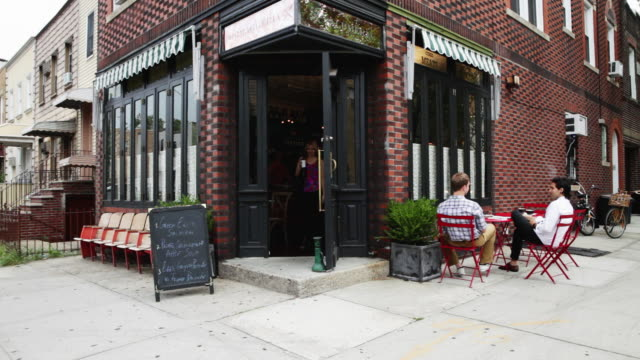 Woman leaving coffee house and greeting men as she walks by