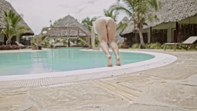 slo mo woman leaving her bungalow to take a swim in the swimming pool - deck chair stock videos & royalty-free footage
