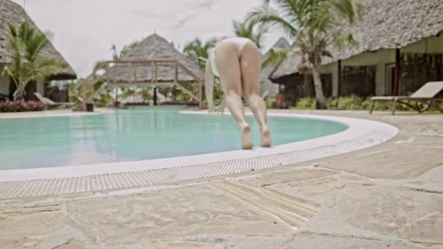 slo mo woman leaving her bungalow to take a swim in the swimming pool - bikini stock videos & royalty-free footage