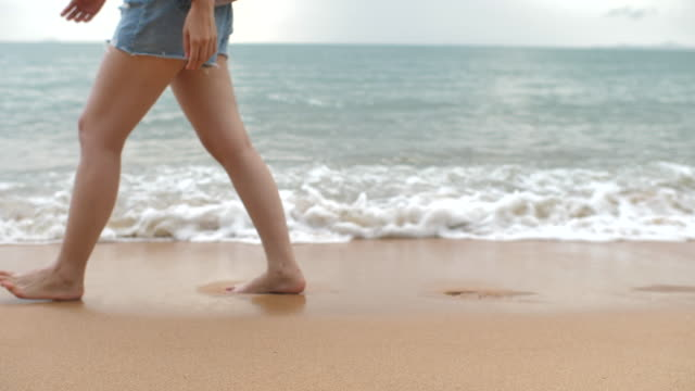 woman leg walking on the sandy beach - scalzo video stock e b–roll