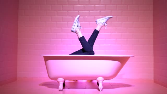 vídeos de stock e filmes b-roll de woman legs having fun in the pink bathtube - ideas