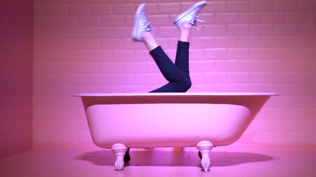 Woman Legs Having Fun in the pink bathtube