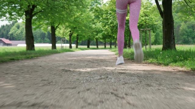 vidéos et rushes de jambes de femme en leggings roses fonctionnant dans le parc - non urban scene