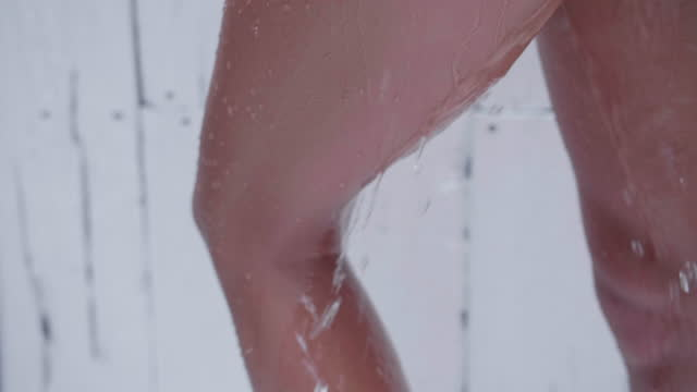 woman legs showering taking a shower at a resort hotel spa bathroom. - slow motion - swimming costume stock videos & royalty-free footage