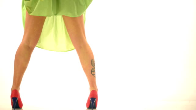 Woman legs with tatoo and high heels on white dots