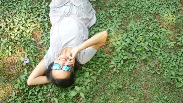 woman lie down on grasses using phone