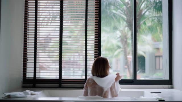 vídeos y material grabado en eventos de stock de mujer se encuentra en un gran baño de espuma - domestic bathroom