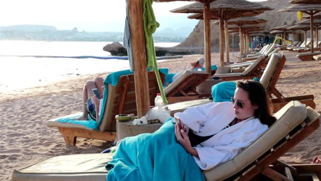 vídeos de stock, filmes e b-roll de a mulher encontra-se em um deckchair e usa o telefone móvel. - chapéu de sol