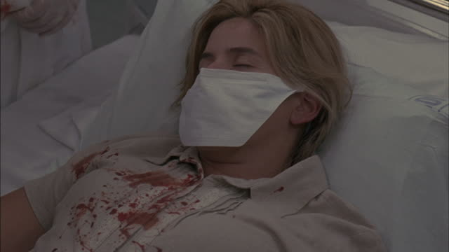 a woman lies on a hospital bed covered in blood. - 病気点の映像素材/bロール