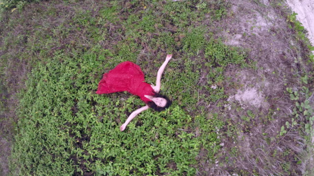 Woman lies on crest of sand dunes by sea, wearing red dress