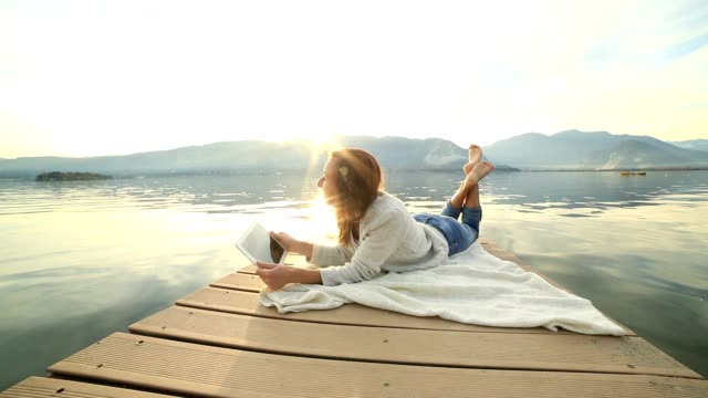 Woman lies on jetty using digital tablet
