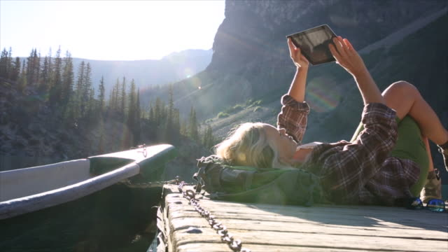 woman lies on wooden lake pier, uses digital tablet, canoe - rucksack stock videos & royalty-free footage