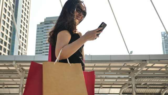 woman lifestyle with shopping bag and smart phone - paying stock videos and b-roll footage