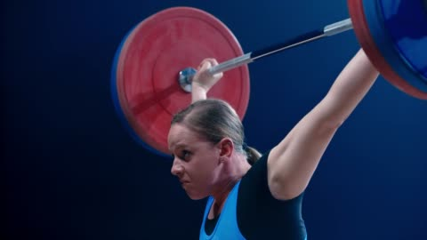 slo mo tu woman lifting a barbell above her head at a competition - picking up stock videos & royalty-free footage