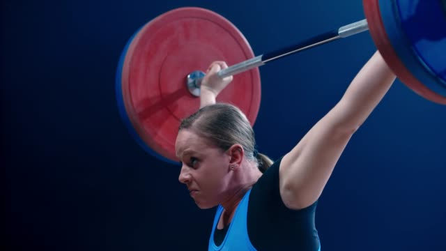 vídeos de stock e filmes b-roll de slo mo tu woman lifting a barbell above her head at a competition - levantar