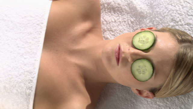 woman lifting cumber slice from eye - cucumber stock videos and b-roll footage
