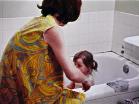 1968 woman lifting small girl up in bathtub + washing her face with washcloth / educational - bambina nuda video stock e b–roll