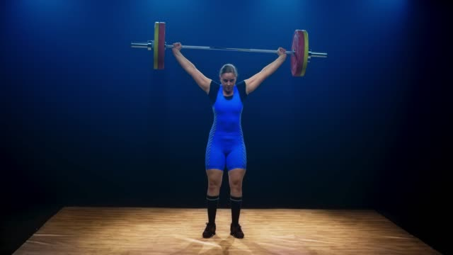 stockvideo's en b-roll-footage met ld woman tillen van de barbell door het uitvoeren van de snatch lift op de gewichtheffen concurrentie - gewicht fysieke beschrijving