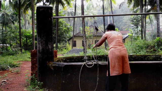 woman lifting water from the well - well structure stock videos and b-roll footage