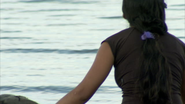 a woman lifts a fishing net and rows a canoe in valdivia, chile. available in hd. - 後ろで束ねた髪点の映像素材/bロール
