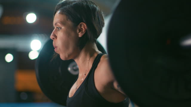 ms, slo mo a woman lifts weights in a gym / rio de janeiro, brazil - sollevare video stock e b–roll