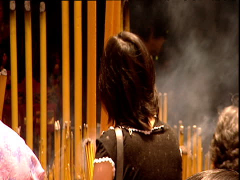 stockvideo's en b-roll-footage met woman lighting bunches of incense sticks in temple courtyard kong hong - gelovige