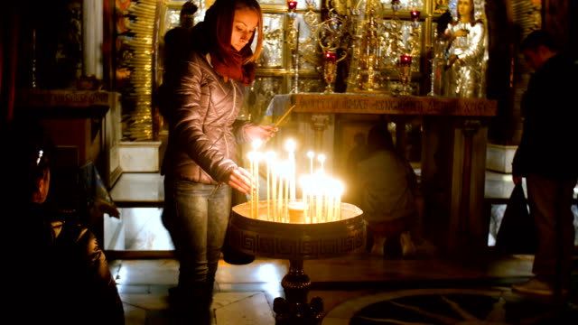 stockvideo's en b-roll-footage met woman lighting candles in the holy sepulchre church/ jerusalem old city - kerk
