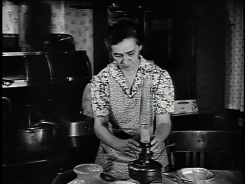 1923 ms woman lighting oil lamp and putting lamp shade on lamp / united states - 1923 stock-videos und b-roll-filmmaterial