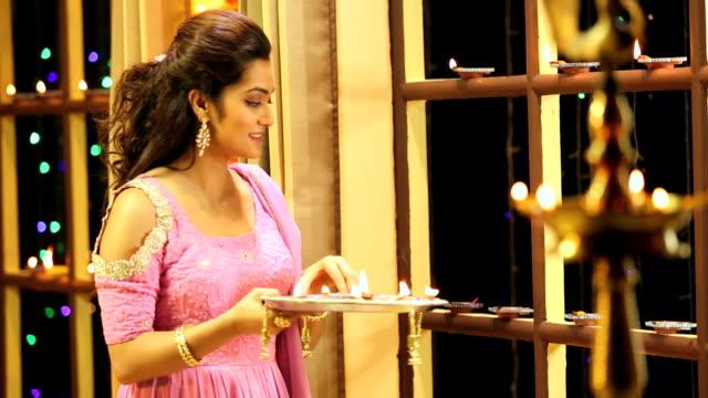 ms woman lighting up oil lamp during diwali festival at home - 盆点の映像素材/bロール