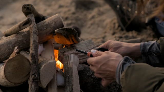 woman lights a fire with driftwood on a beach - fire natural phenomenon stock videos & royalty-free footage