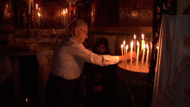 woman lights candles - priester stock-videos und b-roll-filmmaterial