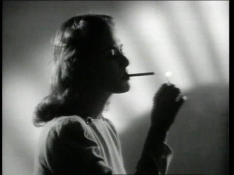 1942 ms woman lights up cigarette in a shadowy room - sigaretta video stock e b–roll