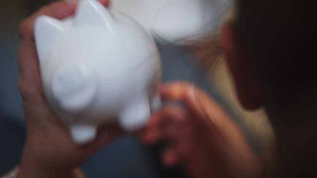 woman listen to the noise of coins in a piggy bank at home. - piggy bank stock videos & royalty-free footage