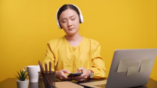 stockvideo's en b-roll-footage met de luisterende muziek van de vrouw en dans over gele achtergrond - in ear koptelefoon