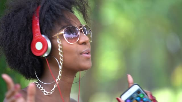 vídeos de stock e filmes b-roll de woman listening music at park - brazilian ethnicity